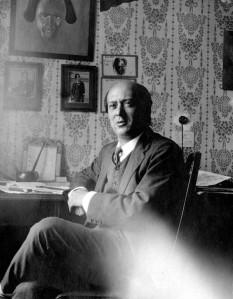 El compositor Arnold Schönberg en 1911, con un retrato de Gustav Mahler a sus espaldas.